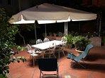 Terrazza in giardino con tavolo, sedie e ombrellone
