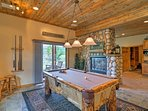 The lower level of the house features a pool table and French doors to a patio.
