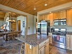 The fully equipped kitchen features stainless steel appliances and an island.