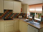 Kitchen overlooking garden, with fridge freezer, dishwasher, electric oven, hob and microwave
