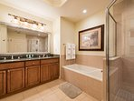 The spacious master bathroom has double sinks, with separate shower and bath