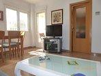Acceso a la cocina y terraza desde la sala de estar con TV