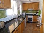 Cocina con vitrocerámica, microondas, horno y lavavajillas