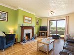 Living room - real log fire & comfy seating for 8 people. Views of the Menai Straits in the distance