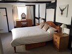 Large bedroom with exposed beams and kingsize bed