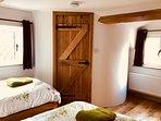 Twin bedroom with dual aspect - with door to spiral between windows.