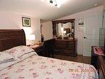 Master bedroom has full dresser, computer desk, 2 chairs, lamp, alarm clock, queen sleigh bed