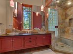 King bedroom en suite with dual vanities, stone shower, and jet tub
