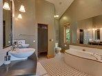 Second en suite bathroom with dual vanities, walk in shower, and jet tub
