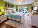 master bedroom downstairs with glass french doors to pool deck area