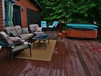 Large deck at main house has a hot tub and cozy furniture to enjoy anytime of the day or night!