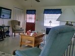 View of living room and front entry, includes cable on 55' TV