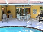 View of covered lanai from pool. Includes table and 4 chairs, lounge chair and grill.