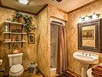 The full bathroom hosts a shower and pedestal sink.