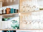 Floating shelves hold a careful selection of drinkware, ideal for entertaining.