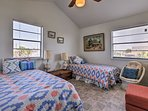 Two twin beds with colorful bedding furnish this first bedroom.