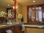 The master bathroom features a deep soaking tub and walk-in shower.