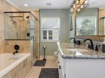 This bathroom features a bathtub, walk-in shower and his-and-hers sinks.