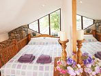 King sized bed on Mezzanine with views of countryside beyond