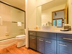 A bathroom in the hallway has a shower/tub combination and a large vanity.