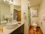 The ensuite bathroom has a modern sink and shower/tub combination.