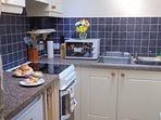 The kitchen, where you will find a cream tea on arrival. T-towels and cleaning materials supplied.