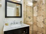 The private bath in the master bedroom offers a relaxing rain shower