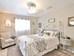 Master bedroom has a queen bed, large windows, chair and decorated in lovely neutral colors.
