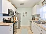 Updated alley style kitchen with tile floors and stainless appliances.