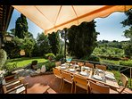 Outdoor terrace with awning and large dining table, overlooking the garden and pool