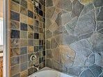 The stonework elevates the bathroom.