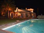 Villa with illuminated pool, pool bar, patio