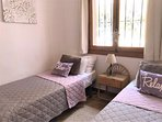 Second bedroom with twin beds and mosquito nets on window