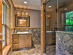 The final bathroom offers a walk-in shower and Travertine tile.