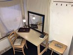 Small cozy room with great natural sunlight features a desk, lamp, space heater, mirror, etc.