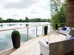 Spacious deck overlooking the tranquil lake with lounge seating & dining table for al fresco eating