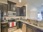 Stainless steel appliances gleam against shining black cabinets.