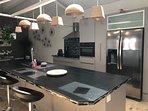 La cuisine avec plaque induction hotte four combiné micro onde frigo américain lave vaisselle/linge