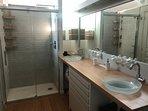 La salle de bain avec double vasque et douche à l'italienne