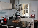 Modern galley kitchen with induction hob and oven, microwave, dishwasher and refrigerator.