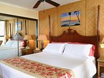 King bedroom and bath, with quality linens, tropical decor.. and view of the ocean