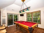 Pool Table Room with TV and Slide Door Access to Hot Tub on Deck
