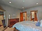 The first bedroom features a queen bed, dresser, and en-suite bathroom.