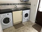 Separate utility room with washing machine and tumble drier
