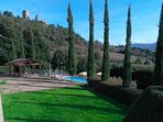 The cypresses and the pratino in front of the villa with View of the village of Montceastell Pisano