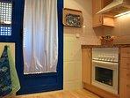 Cocina con horno y vitro. Lavavadora en el tendedero.