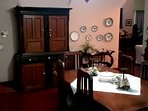The beautifully furnished Dining room with its polished silver, fine china & antique wall plates wit