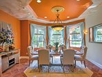 The elegant dining room features 6 tufted chairs around the elongated table.