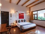 Ground floor bedroom with faux wood floors and a large window overlooking the garden