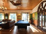 Large glazed french windows in the living area allow for an abundance of natural light to play pool